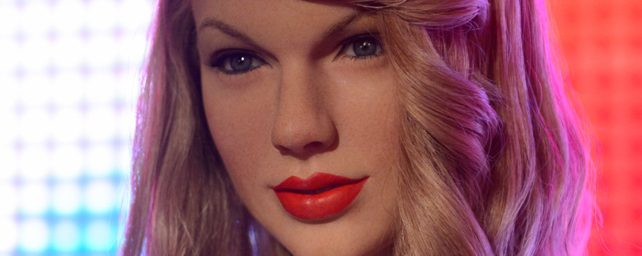Taylor Swift- The medium blond flaxen color is drab and the bang curl is a bad rertro idea