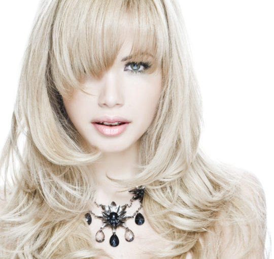 Very Femine Sexy  Womans Haircut With Medium Length Layers and Bang.  Light Ash Blond Hair Color