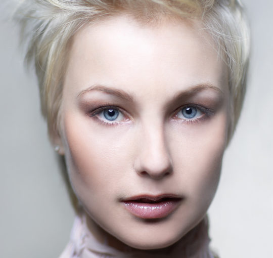 A short pixie hair cut left long on top to where different ways.  Set off by Platinum hair color.