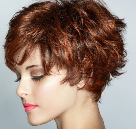 Short choppy shag brunette colored with red copper highlights throughout.