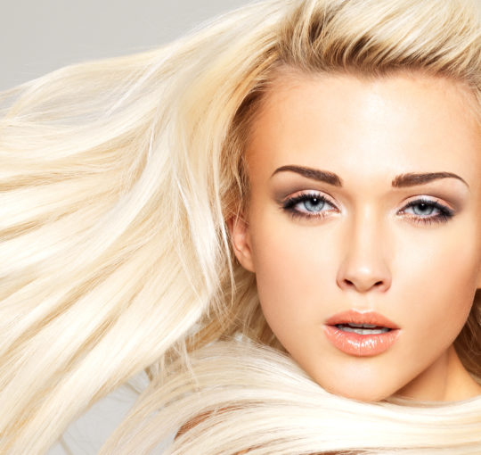 Elegant looking vanilla blond hair color on gold roots on dramatic one length hair cut
